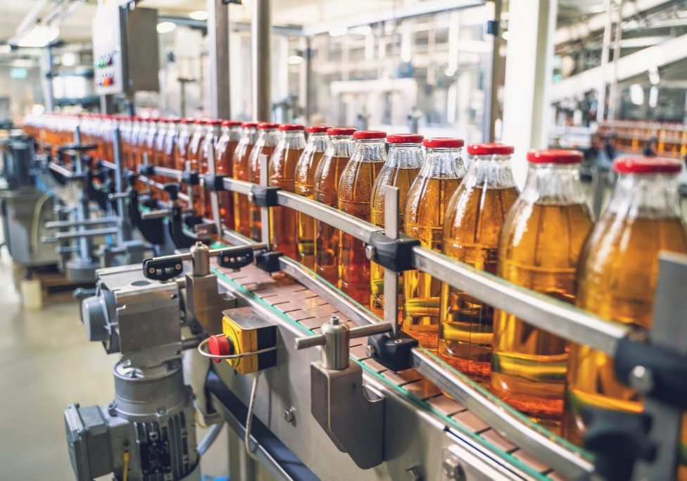Conveyor belt, juice in glass bottles on beverage plant or factory interior, industrial manufacturing production line, toned